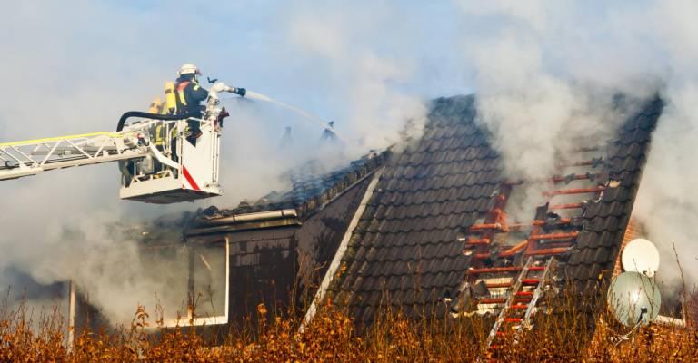 Brandweerman is brand aan het blussen van een huis